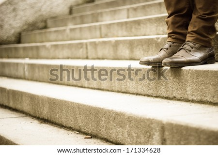 Walking downstairs: close-up view of man's leather shoes  (color toned image) - stock photo