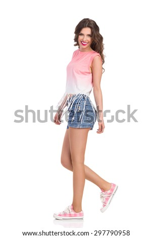 Walking Girl In Jeans Shorts And Sneakers. Full length studio shot isolated on white. - stock photo