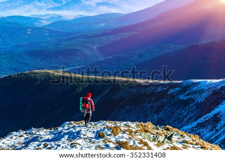 Walking Hiker in Red Jacket with Backpack on Snow Slope distant Mountain Ridges stacked on Background warm Sunlight
