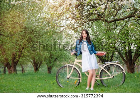 Walking in the spring garden. Attractive young brunette woman standing with a bicycle against nature background. - stock photo