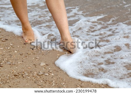 walking on sandy beach - stock photo