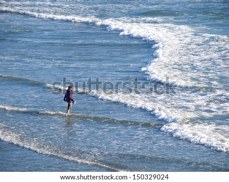 Walking on the beach along the waters edge - stock photo