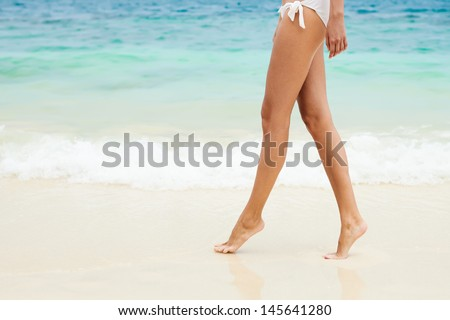 Walking on the beach. Close up on legs walking along the sea side