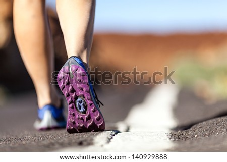 Walking or running legs on mountain road, adventure and exercising in summer nature. Female hiker or runner foot and sport shoes doing workout outdoors. - stock photo
