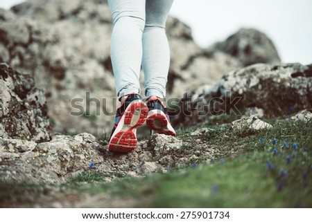Walking or running legs on trail, adventure and exercising concept. Toned image