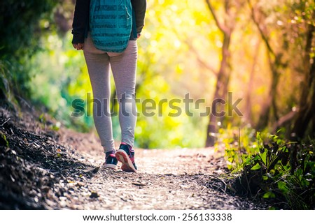 Walking or running legs on trail, adventure and exercising in forest at sunset - stock photo
