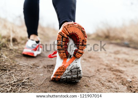 Walking or running legs sport shoes, fitness and exercising in autumn or winter nature. Cross country or trail runner outdoors. - stock photo