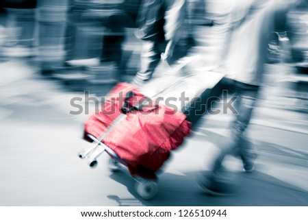 walking passenger with traveling case blur motion - stock photo