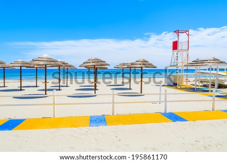 Walking path along sandy Porto Giunco beach with lifeguard tower and sun umbrellas, Sardinia island, Italy  - stock photo