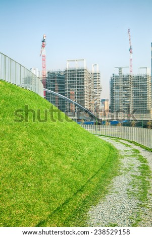 Walking path with green grass and construction site  - stock photo