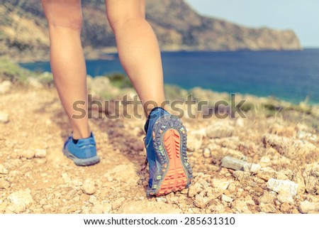 Walking running hiking or exercising, sports shoe and legs on rocky hiking trail in mountains, motivation inspiration concept outdoors, achievement fitness adventure and exercising in wild nature - stock photo