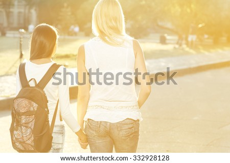 Walking side by side. Horizontal shot from behind of mother walking her teen daughter with a backpack to school holding hands - stock photo