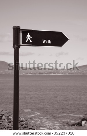 Walking Sign against Sea Background in Black and White Sepia Tone