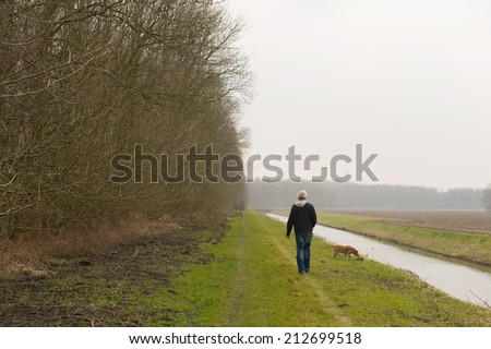 Walking the dog in Dutch flevopolder - stock photo