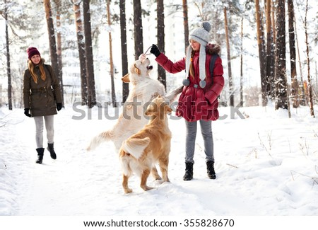 Walking the dog in the park in winter. Two girls. Two sisters playing with a dog. Two golden retriever playing in the snow in the woods. - stock photo