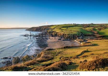 Walking the South West Coast Path as it descends from Dodman point to Hemmick Beach on the south coast of Cornwall - stock photo