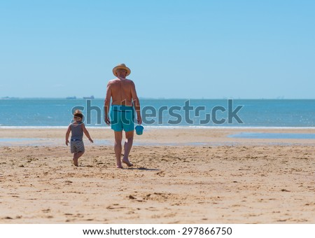 walking to the sea with a bucket - stock photo