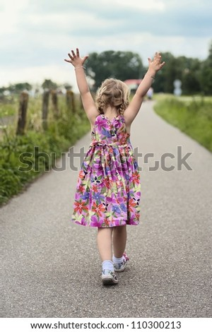 Walking toddler with her hands up in the air