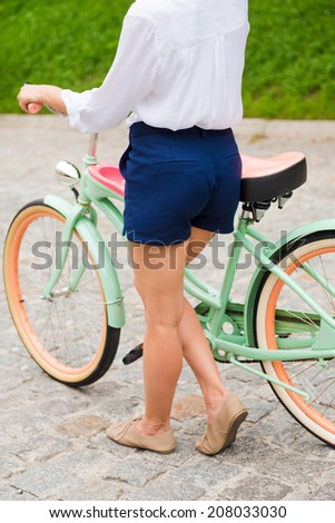 Walking with bicycle. Close-up of young woman walking with bicycle - stock photo