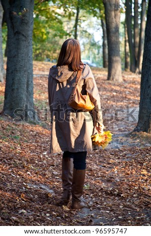 walking woman in autumn park - stock photo