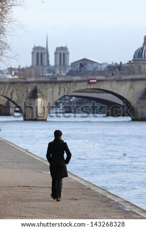 Walking woman on the banks of the Seine river in Paris - stock photo