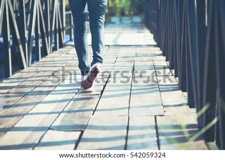 Walking women jeans and shoes with sun light