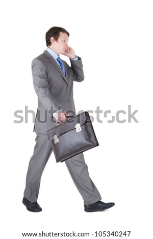 walking young businessman with briefcase isolated on white background