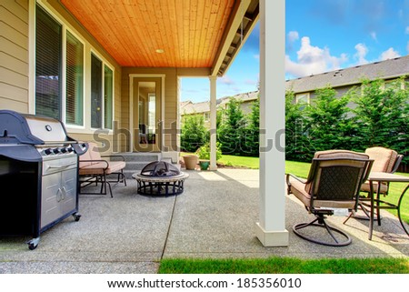Walkout deck with fire pit, settee, patio table set and barbecue - stock photo