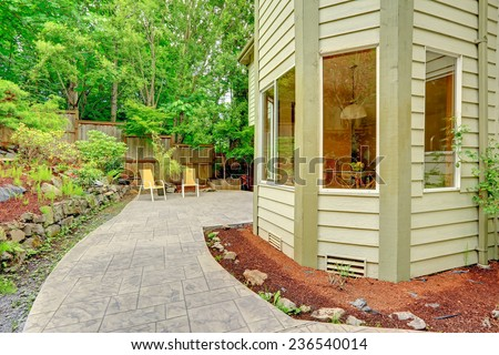 Walkout patio with sitting area and backyard leveled landscape design with stones.  Tile walkway - stock photo