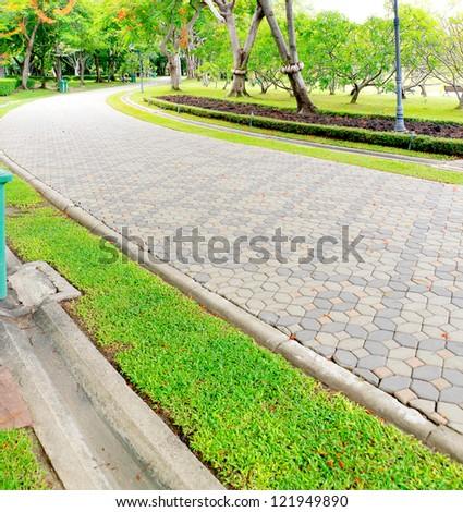 Walkway made of bricks in various colors at garden. - stock photo