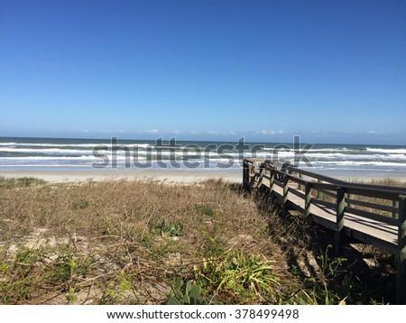Walkway to ocean over sand dune - stock photo