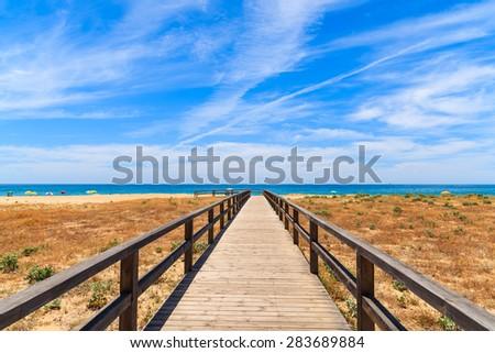 Walkway to sandy beach in Armacao de Pera coastal town, Algarve region, Portugal - stock photo