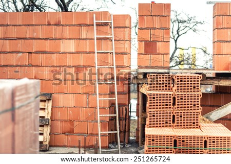 Wall building with professional bricks, construction site of new house - stock photo
