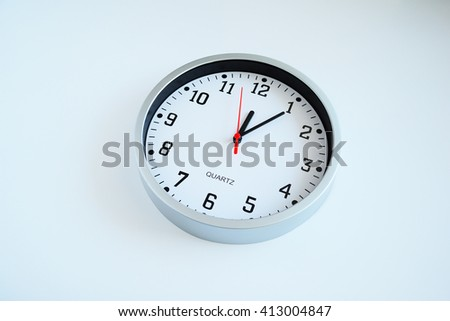 Wall clock isolated. Round white quartz clock on the white background. White face, black clockwise and numbers, red second hand, time on the clock is 12-05. 5 minutes on clock.