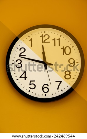 Wall clock with the order of the numbers inverted on a colored background - stock photo