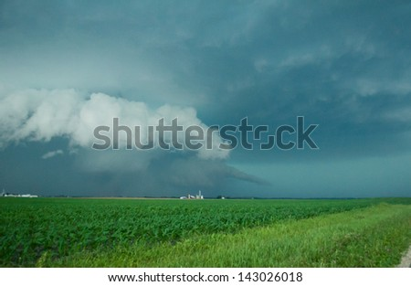 Wall cloud with rain wrapped tornado and tail cloud. - stock photo