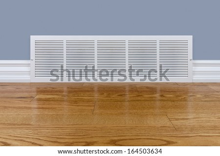 Wall cold air return grille sitting on hardwood floor - stock photo