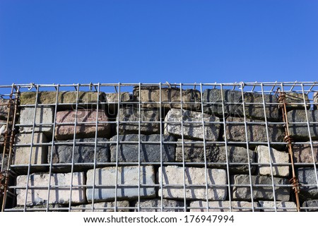 Wall constructed using gabion cage method. - stock photo