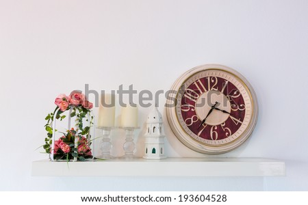 wall decorated with clocks ,flower and candle - stock photo