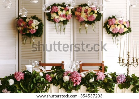 Wall floral decorations of roses and hydrangeas in a restaurant above the wedding table with food. Luxury floral compositions
