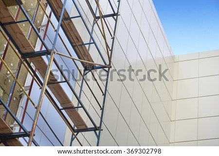Wall insulation, mineral wool, composite panels cladding of buildings, resource conservation, scaffolding, carrying out aerial work, insulation of facades, building material, building facing work. - stock photo
