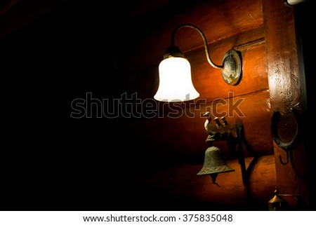 Wall lamp and a bell with a duck on it attached to the side of the log cabin wall