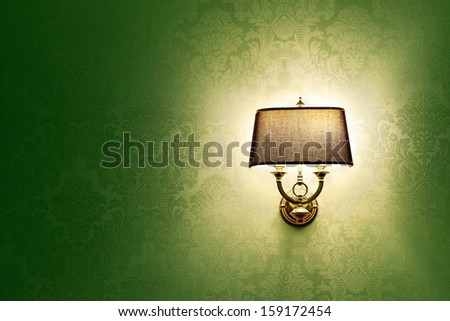Wall lamp with a shade on the background of green Wallpaper - stock photo