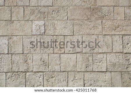 Wall made from limestone bricks of regular shapes and white color slotting together precisely. Close up architecture photography. Creative wallpaper photography. - stock photo