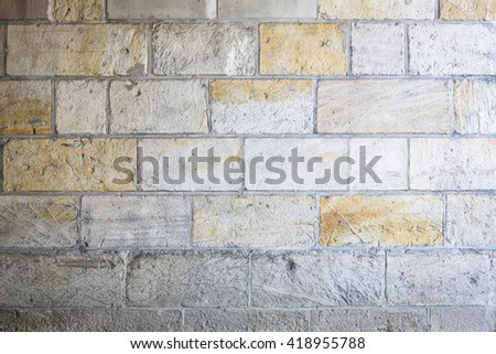 Wall made from sandstone bricks of regular shapes and different color slotting together precisely. Close up architecture photography. Creative wallpaper photography.