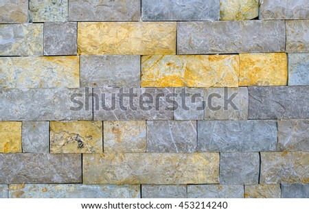 Wall made of stone blocks of various coloration and of natural texture, as a background. - stock photo