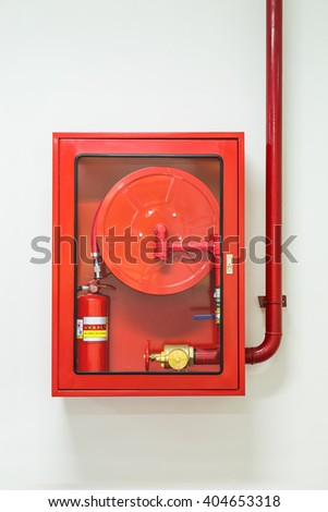 Wall mounted fire hose and extinguisher cabinet and water plumbing - stock photo