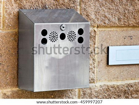 Wall-mounted stainless steel cigarette bin on an exterior wall outside a place of work where smoking is banned inside. This enables smokers to extinguish and dispose of cigarettes.