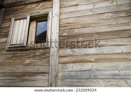 Wall of an wooden cottage with a small window - stock photo