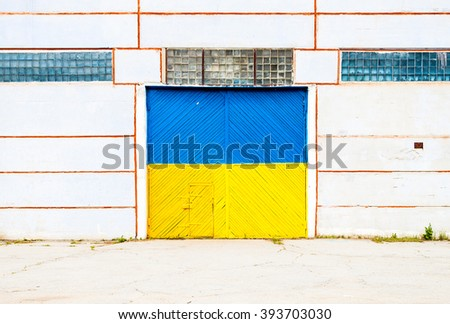 Wall of ancient warehouse with door painted in ukrainian flag colors - blue and yellow. Ukrainian flag on the background of old locked doors - stock photo